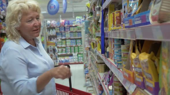Cover Image for Senior Woman Is Choosing Canned Pet Food About Supermarket's Aisle with Shop Basket