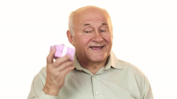 Cover Image for Happy Grandpa Smiling Listening To a Gift Box Guessing What Is Inside