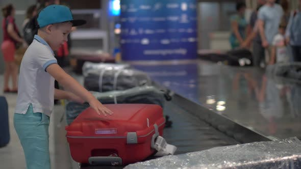 Thumbnail for Boy Looking for His Suitcase on Baggage Conveyor Belt at the Airport