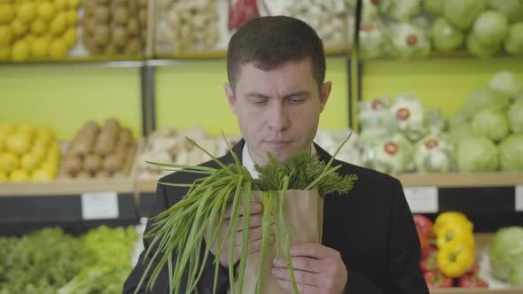 Thumbnail for Front View of Satisfied Caucasian Man Smelling Fresh Greenery Bunch and Stretching It To Camera
