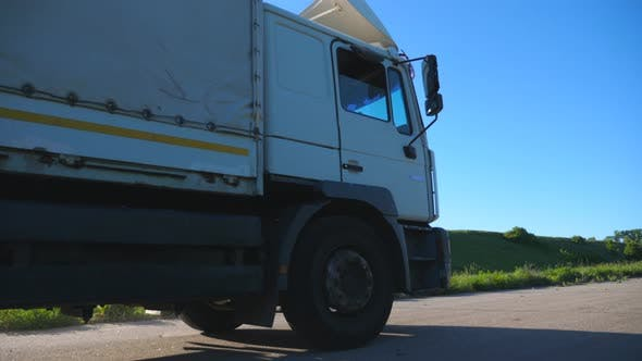 Thumbnail for Camera Follows To Truck with Cargo Trailer Driving on Highway and Transporting Goods at Sunny Day