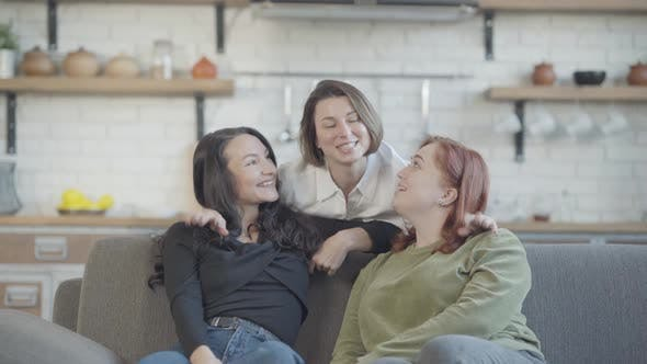 Thumbnail for Charming Slim Woman Hugging Friends Sitting on Couch and Talking