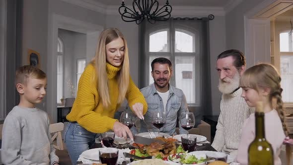 Thumbnail for Woman Carving Tasty Roast Turkey for Her Relatives which Sitting at the Festive Family Table