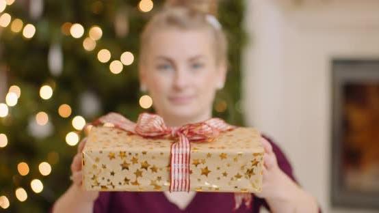 Thumbnail for Junge Frau zeigt Ihr Weihnachtsgeschenk zu Hause