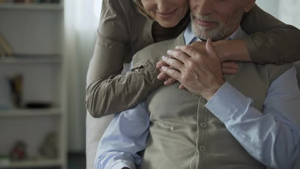 Thumbnail for Male Retiree Reading Newspaper, Female Hugging from Behind, Loving Tenderness