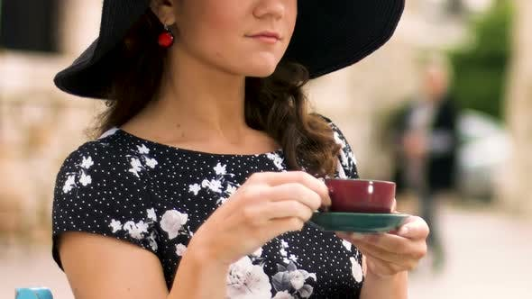Thumbnail for Intelligent Woman in Hat Drinking Coffee at Street Cafe Enjoying Vacation