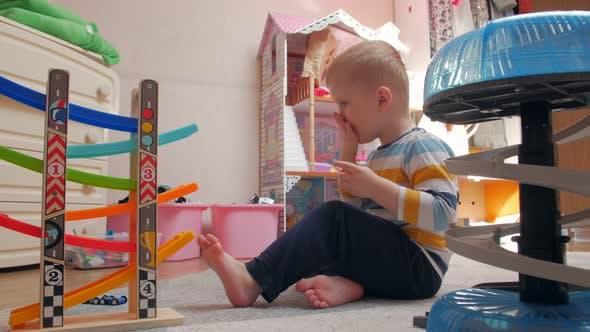 Kleiner Junge spielt und kaut Sandwich