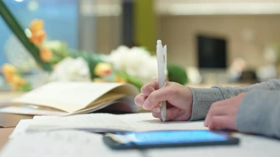 Cover Image for Woman study the note on paper with mobile phone at library