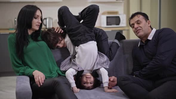 Happy Father and Mother Watching TV As Twin Sons Having Fun Grimacing on Couch