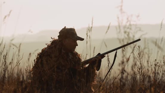 Cover Image for Hunter in Hunting Equipment Lies in Wait in Sunset Light, Saw the Target and Aim with Shot Gun