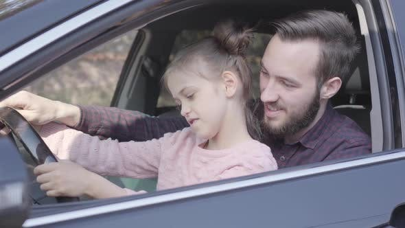 Thumbnail for Little Girl Sitting on Father's Lap in the Car Holding Wheel Close Up. The Child Is Learning To
