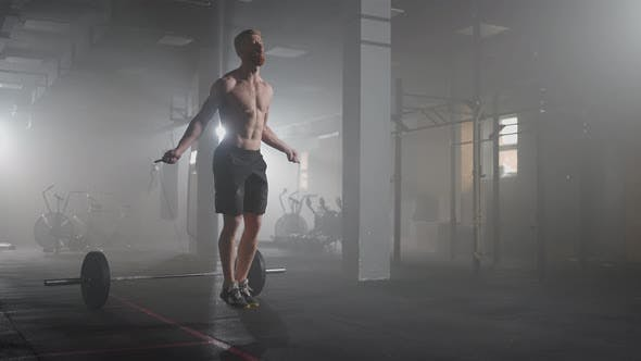 Young Man Exercising Using Skipping Rope in Gym