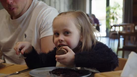 Little Girl With Dad In A Cafe Eating Dessert