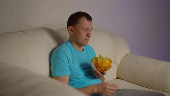 A Young Man with a Bowl of Chips Sits on the Couch in the Evening and Looks