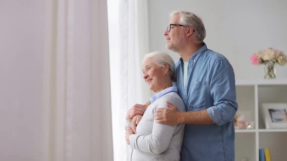 Thumbnail for Happy Senior Couple Looking Through Window at Home