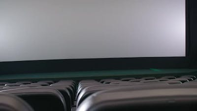 Rows of Theater Seats and White Screen
