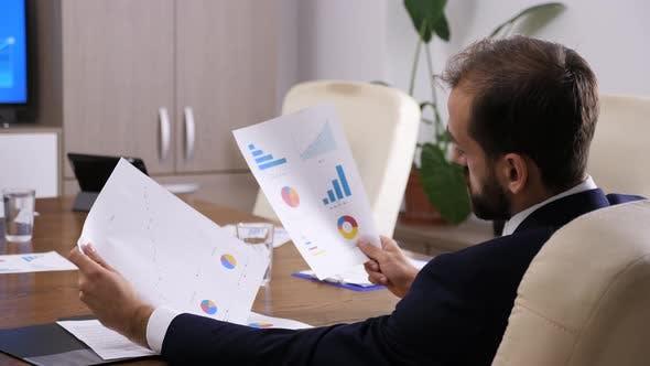 Thumbnail for Businessman Looking at Charts and Graphs