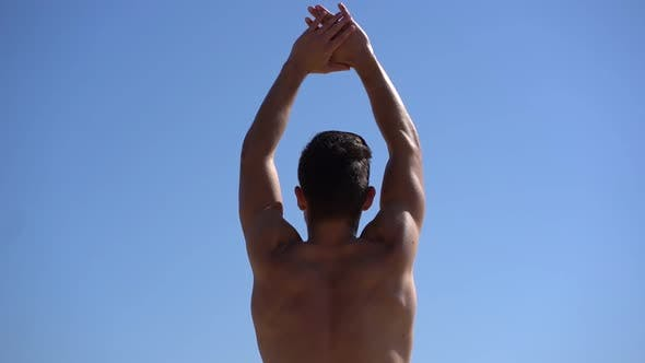 Thumbnail for Shirtless Muscular Man Stretching Arms Against Blue Sky