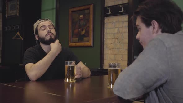 Thumbnail for Two Men Drinking Beer Sitting at a Table in a Pub