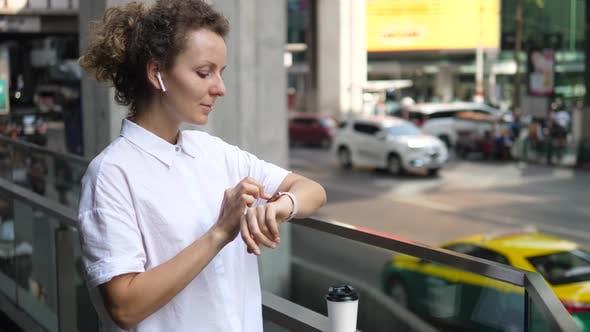 Frau mit Smartwatch In Wireless-Kopfhörer In Stadt