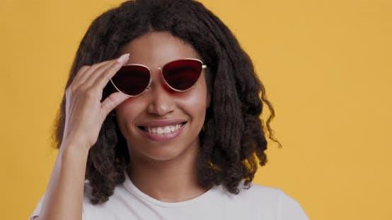 Thumbnail for Playful Black Girl Raising Sunglasses Up and Winking