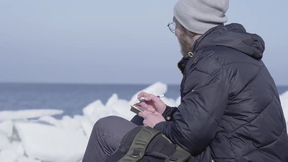 Thumbnail for Handsome Blond Bearded Man Sitting Among the Ices Writing His Observations in a Notebook. Polar