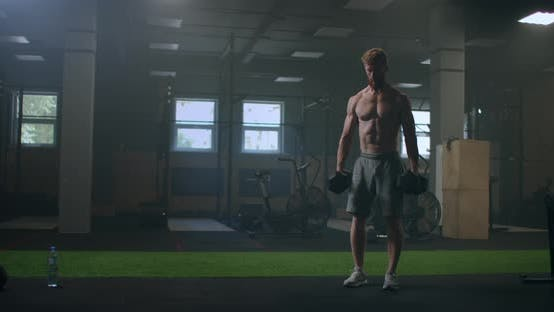 Thumbnail for a Man Without a Shirt Trains By Lifting Dumbbells in the Gym