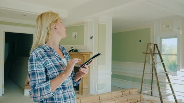 Thumbnail for A Female Designer Uses a Tablet, Stands in a Room of a New House, Where Repair Is Not yet Complete