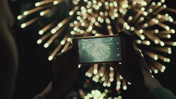 Thumbnail for Silhouette of a Man Photographing Fireworks at Night Sky