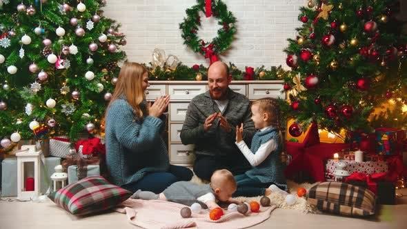 Thumbnail for NEUES JAHR - die Familie in Silvesteratmosphäre spielt Pat-a-Kuchen in der Nähe des Weihnachtsbaumes