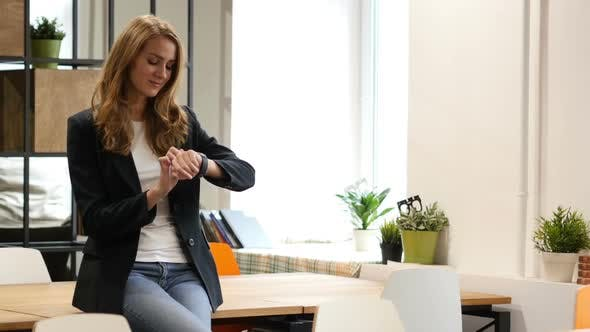 Thumbnail for Using Smartwatch, Business woman Sitting on Desk in Office
