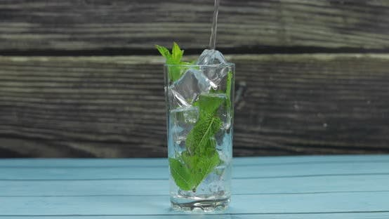 Thumbnail for Clear Water Pouring in Glass with Green Mint Leaves and Ice Cubes