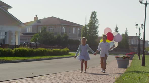 Thumbnail for Little Boy and Girl Walking Outdoors with Balloons