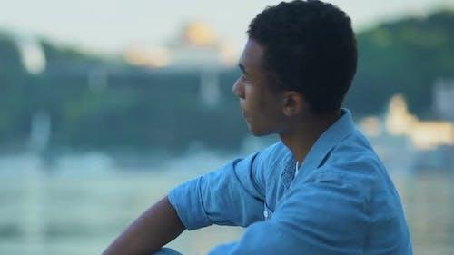 African-American teen boy throwing stones in city lake