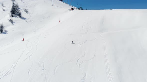 Thumbnail for Aerial: one person skiing on snow in Sestriere ski resort, Turin Italy
