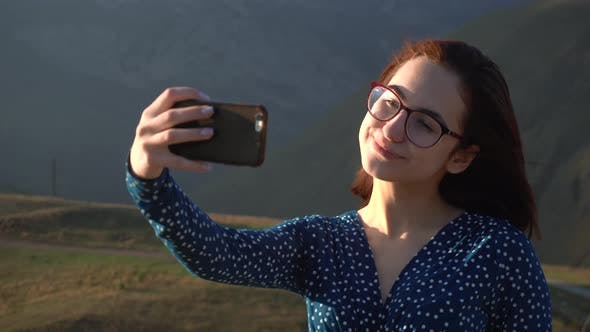 A Young Woman in a Dress Stands in the Mountains and Takes a Selfie on a Smartphone. The Girl