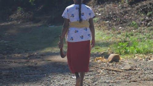 Woman Having Braid with Machete Walks Along Dirty Road