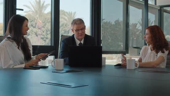 Group of three people meeting in an office to discuss a business project. Slow motion