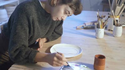 Artist woman working with ceramic plate in the art workshop