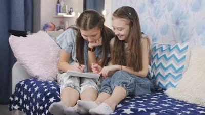 Girls Together on the Bed Draw in a Notebook While Staying at Home in the Children's Room