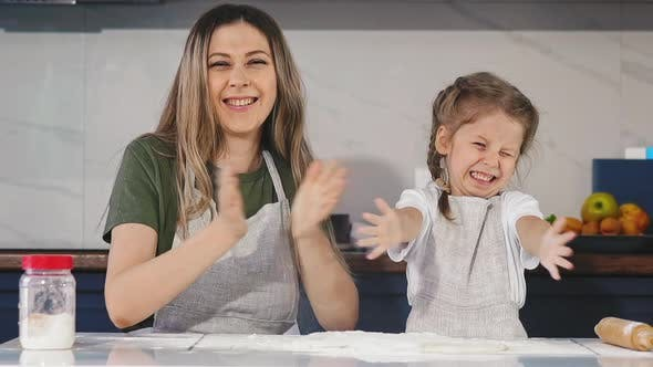 Thumbnail for Family of Little Daughter and Mother Claps Hands with Flour