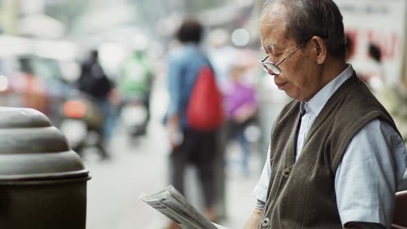 Thumbnail for Handheld view of Vietnamese senior man reading newspaper. Shot with RED helium camera