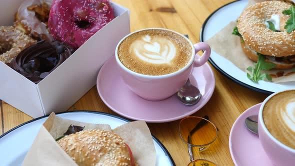 Frühstück mit Kaffee, Bagels und Donuts. Stilvolle trendige Sommerkomposition.