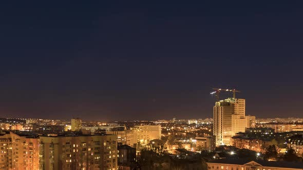 Night Cityscape and Large Tower Cranes Build Multistorey Buildings
