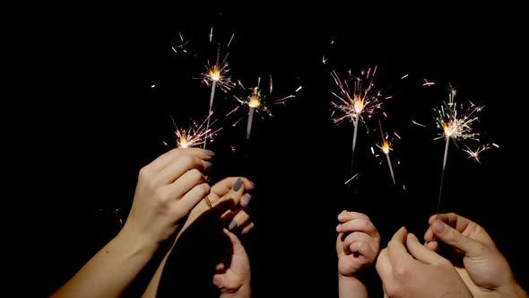 Thumbnail for Closeup Hands Holding Waving Bengal Fire Burning Sparklers Front Black Background