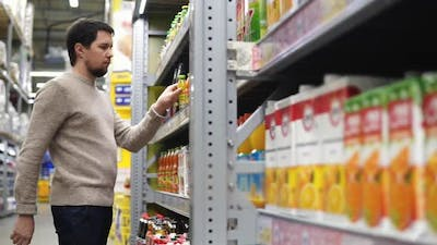 Young Manin the Supermarket Chooses the Packaged Juice