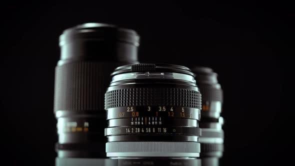 Vintage 50mm Camera Lens Spinning On Black Studio Background