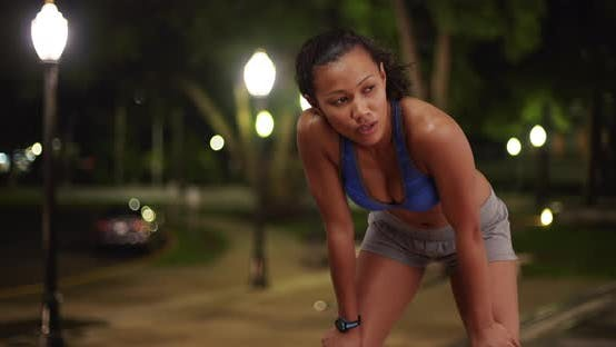 Thumbnail for Toned mixed race woman athlete running outdoors at night