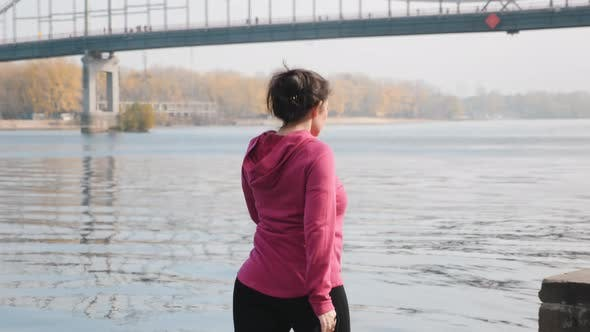 Thumbnail for Young chubby girl doing morning nordic walking exercise alone river and city park