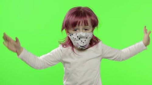 Little Girl in Medical Face Mask. Grabs Her Head in Fear. COVID-19 Coronavirus